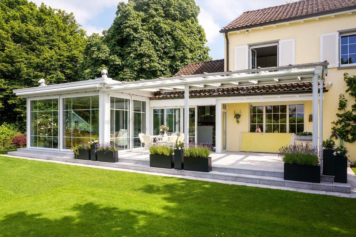 Eleganter Flachdachwintergarten mit Sprossen im Glas und anschliessender Pergola