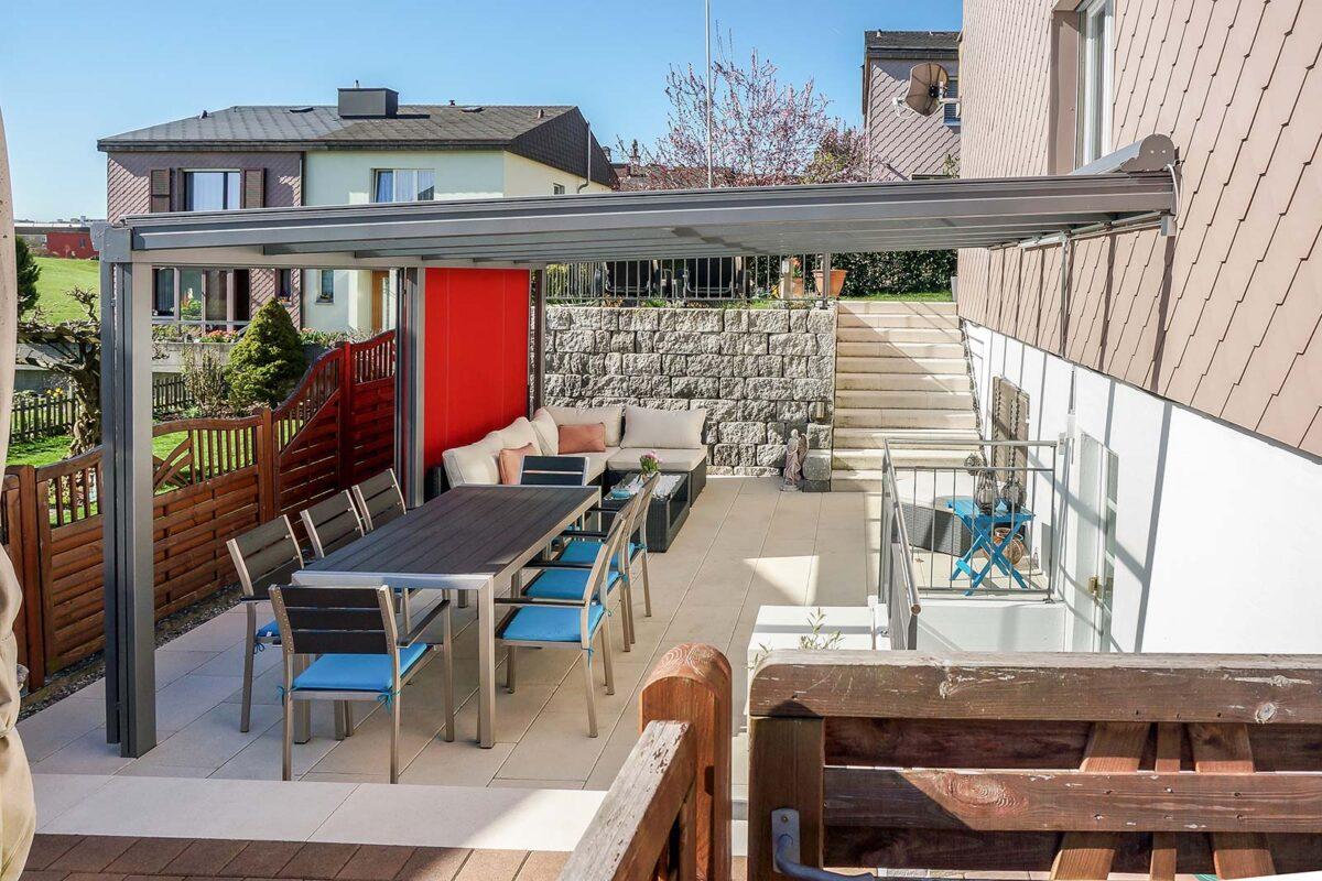 Terrassenüberdachung mit Glasdach und aufliegender Sonnenstore sowie Senkrechtmarkisen in auffälligem rot