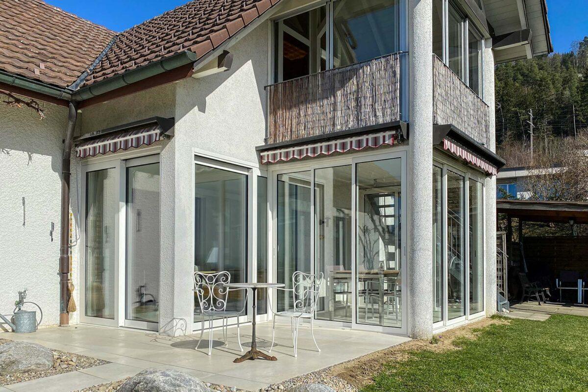 Neue Fassadenverglasung mit 3-fach Isolierglas und Thermoslide80 Schiebewand. Vorne eine Ideal 38 Schiebewand mit Isolierverglasung als top Wind- und Wetterschutz.