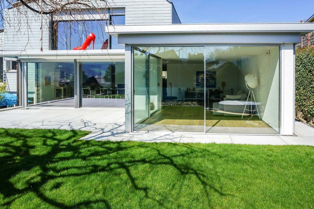 Fassadenverglasung mit rahmenlosen Schiebefenstern