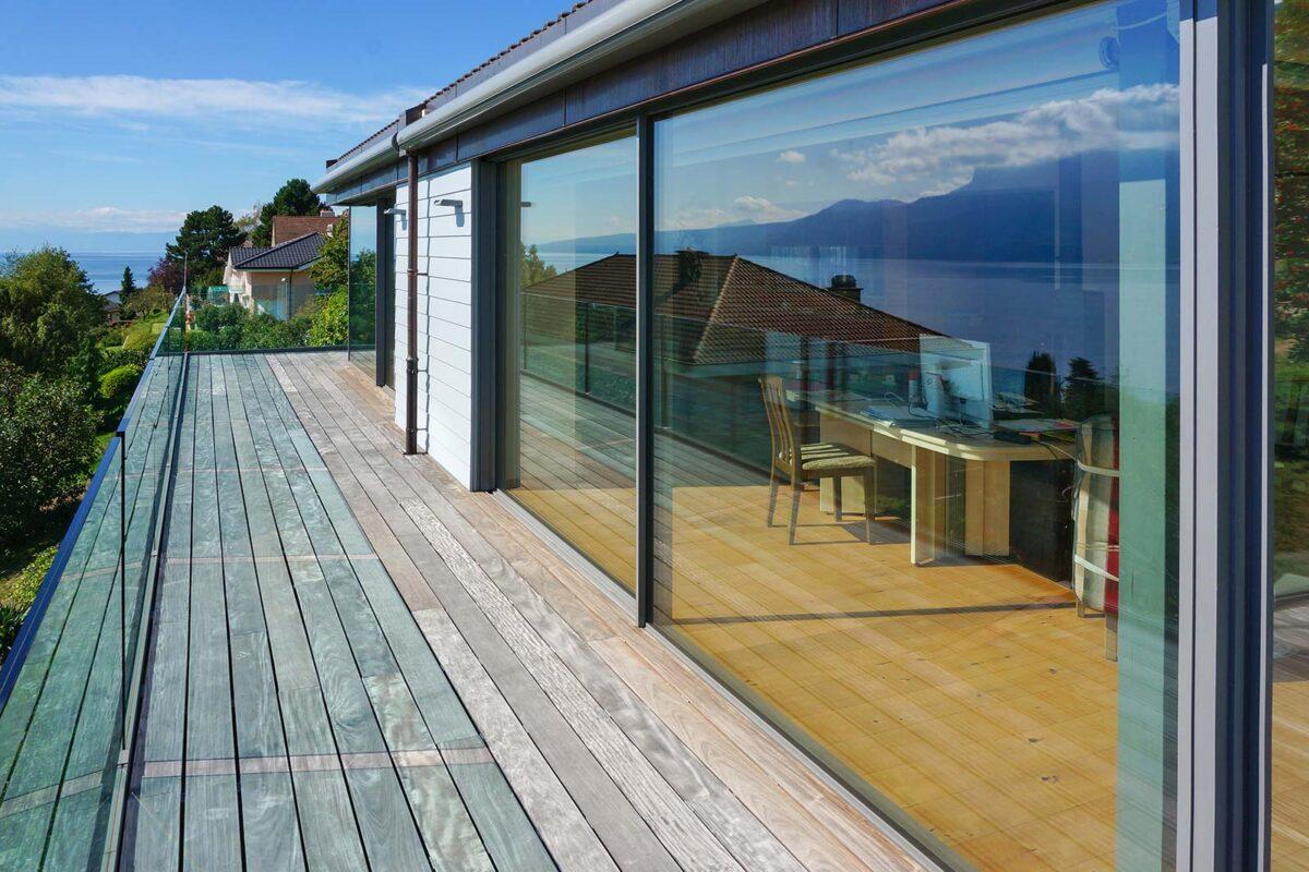 Rahmenlose Schiebefenster - der Kunde geniesst den Ausblick über den Genfersee