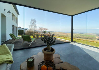 Vollglasschiebewand – Sitzplatzverglasung – Terrassenverglasung – Wind-Wetterschutzverglasung – Sommerverglasung – VG17 – VG15 – Ideal38 – ISO41 – geschützte Terrasse – Schiebeverglasung -